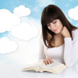 Girl absorbed in reading a book on background with sky and white — Stock Photo #51020929