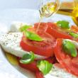 Fresh tomato and mozzarella salad with basil leaves and olive oil — Stock Photo #34226813