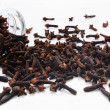 Cloves spilling from glass jar — Stockfoto