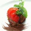 Brownie garnished with strawberries mint and chocolate sauce — Stock Photo