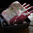 Uncooked rib of beef in roasting tin on wooden top — Stock Photo