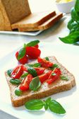 Tomato and basil being prepared into sandwich — Stock Photo