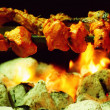 Chicken Tikka on spit cooked over charcoal barbecue — Stock Photo