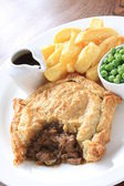 Steak pie with fries and peas plated meal — Stock Photo