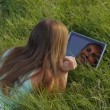 Brunette in meadow using a digital tablet — Stock Video