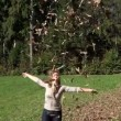Autumn leaves falling on young woman — Stock Video