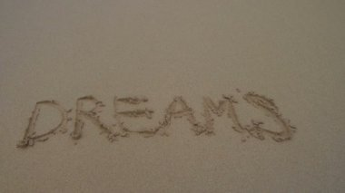 Word dreams written in sand — Stockvideo