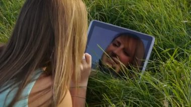 Young woman with tablet in a meadow — Stock Video