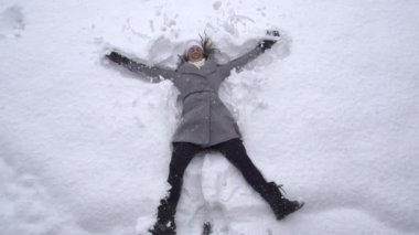 Woman making snow angels — Stock Video