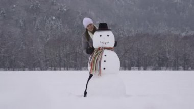 Young woman building a snowman — Stock Video