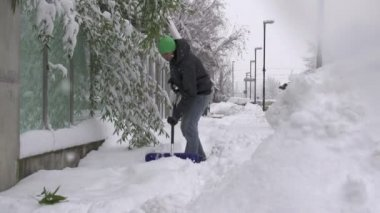 Man removing snow off a sidewalk — Stockvideo