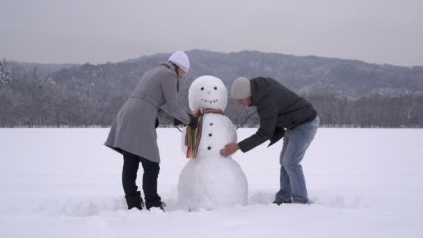 Pareja joven construir un muñeco de nieve — Vídeo de stock