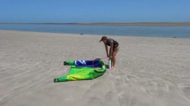 Female kiteboarder inflating a kite — Stock Video