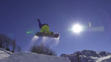 Snowboarder jumping over the sun — Stock video
