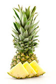 Half pineapple and slices on a white background — Stockfoto
