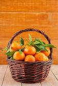 Ripe tangerines with leaves in a basket — Stock Photo