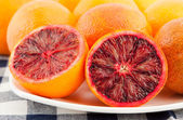 Ripe red blood oranges and slices in the plate — Stock Photo