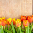 Bouquet of yellow and orange tulips on a wooden background — Stock Photo