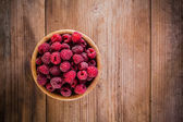 Organic raspberries in a bowl on wooden background — Stock Photo