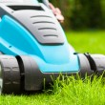 Blue lawn mower on green gras — Stock Photo #49471921