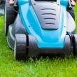 Blue lawn mower on green gras — Stok fotoğraf #49472005
