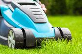 Blue lawn mower on green gras — Stock Photo