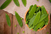 Young green peas pods in a bowl on a wooden background — Stock Photo