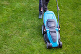 Man with an electric mower on green grass — Stock Photo