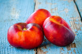 Fresh organic flat nectarines on an old wooden background — Stock Photo