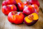Fresh flat nectarines on a wooden background — Stock Photo