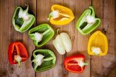 Halves of red, green, black, white and yellow bell peppers — Stock Photo
