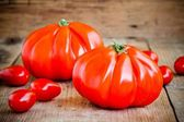 Fresh red heirloom tomatoes on a wooden background — Foto Stock