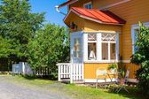 Wooden yellow house with red roof in Scandinavian style — Stock Photo