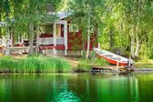 Old red Finnish summer cottage at a lake  — Stock Photo
