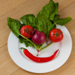 Vegetable face on a white plate — Stock Photo