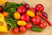 Fruits and vegetables spilling out of a yellow bag — Stock Photo