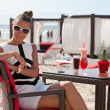 Pretty young woman relaxing on the beach restaurant — Stock Photo
