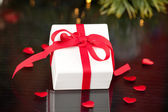 Gift with red ribbon with hearts — Stock Photo