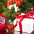 Engagement Ring in Box and Luxury present in red ribbon — Stock Photo