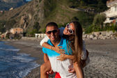 Beautiful young couple having fun on the beach — Stock Photo