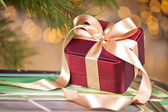 Christmas present on festive lighted background — Stock Photo