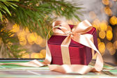 Elegant gift box on defocused lights background — Stock Photo