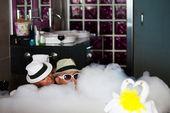 Loving couple lie in a bathroom with bath-foam. — Stock Photo