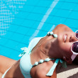 Beautiful young woman relaxing near the swimming pool — Stock Photo #38586561