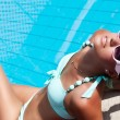 Beautiful young woman relaxing near the swimming pool — Stock Photo #38895175