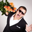 Portrait a young man in suit with bouquet of roses — Stock Photo
