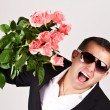Happy romantic husband holding rose flowers. — Stock Photo