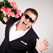 Portrait a young man in suit with bouquet of roses — Stock Photo #39849579