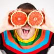 Smiling man holding two grapefruits in hands — Stock Photo #39849977