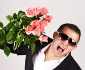 Happy romantic husband holding rose flowers. — Stock Photo